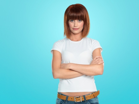 shy woman: beautiful, young woman smiling with her arms crossed, on blue background Stock Photo