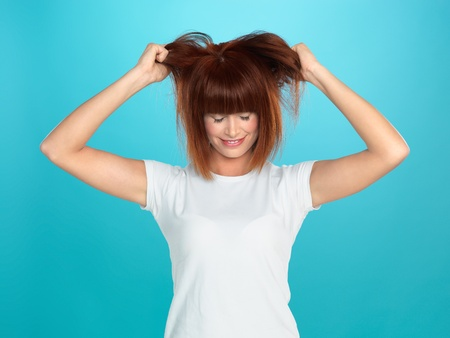 pulling hair: beautiful, young woman pulling her hair, on blue background Stock Photo