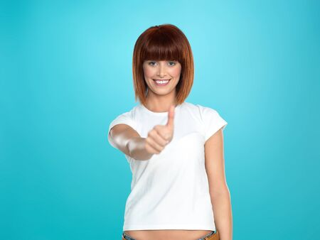 beautiful, young woman smiling and showing an ok sign with her hand, on blue background photo