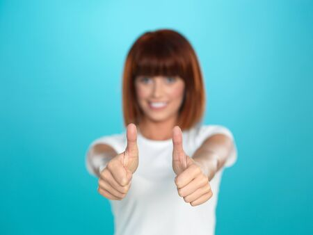 beautiful, young woman smiling and showing an ok sign with her hands, on blue background photo
