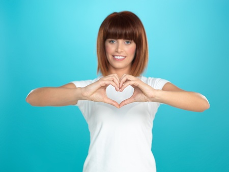 chest hair: beautiful, young woman smiling and making a heart shape with her hands, on blue background Stock Photo