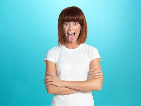 beautiful, young woman smiling and showing her tongue, on blue background photo