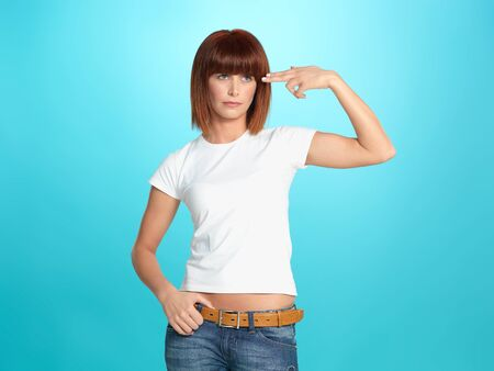beautiful, young woman pretending to shoot a gun at her head, on blue background Stock Photo - 13239822