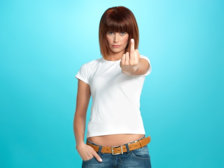 beautiful, young woman showing the middle finger, on blue background photo