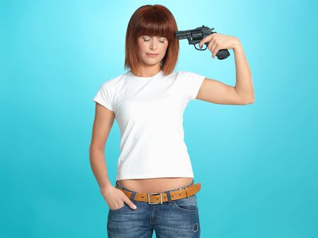 negative spaces: beautiful, young woman pointing a gun at her head, on blue background