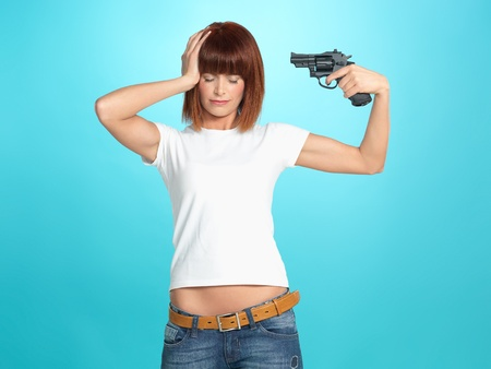 holding gun to head: beautiful, young woman pointing a gun at her head, on blue background