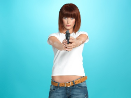 agressive: beautiful, young woman pointing a gun at the camera, on blue background