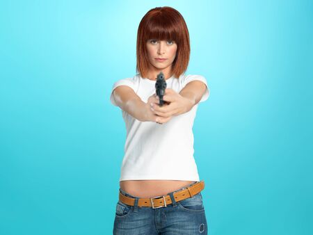 beautiful, young woman pointing a gun at the camera, on blue background Stock Photo - 13239377