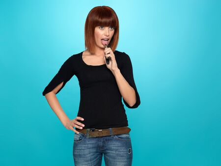 freak out: beautiful, young woman pulling her tongue with a pliers, on blue background Stock Photo