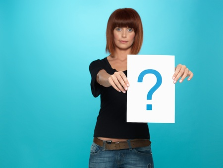 beautiful, young woman showing a question mark on a white piece of paper, on blue background photo