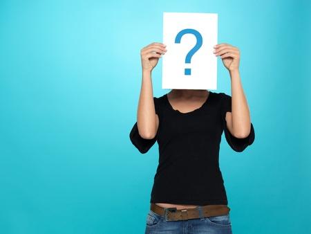 signo de pregunta: mujer hermosa, joven que muestra un signo de interrogaci�n en un pedazo de papel blanco en la parte delantera de su cabeza, sobre fondo azul