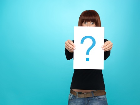 asking question: beautiful, young woman showing a question mark on a white piece of paper, on blue background