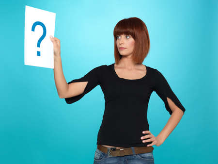 beautiful, young woman looking at a question mark on a white piece of paper, on blue background photo