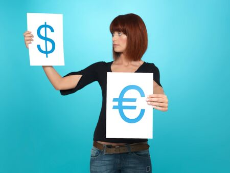 beautiful, young woman showing and comparing a dollar and an euro symbol, on two pieces of paper, on blue background Stock Photo - 13239542