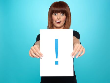 beautiful, young woman showing an exclamation mark on a piece of paper, on blue background photo