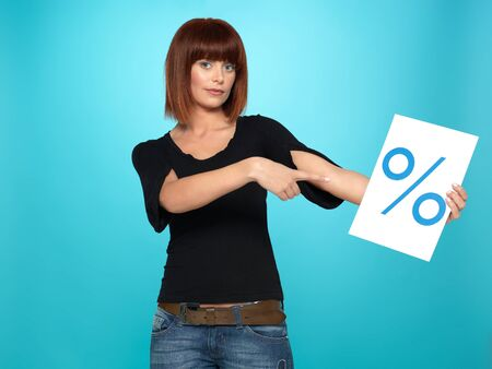 beautiful, young woman showing a percent sign, on blue background Stock Photo - 13239880