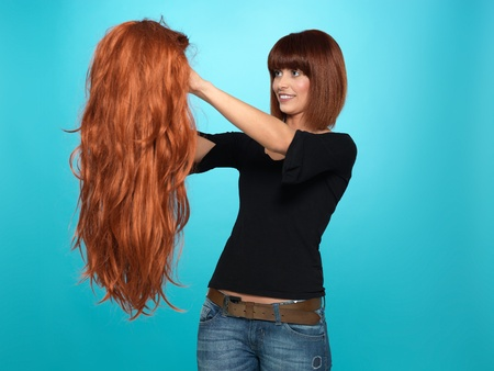 artificial hair: beautiful, young woman admiring a long, red hair wig she is holding, on blue background Stock Photo