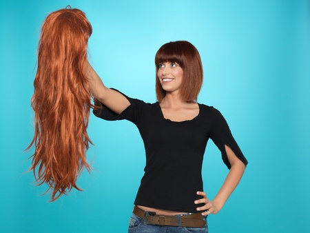 alter ego: beautiful, young woman admiring a long, red hair wig she is holding, on blue background Stock Photo