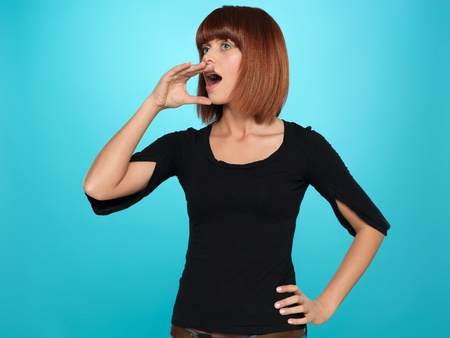 beautiful, young woman shouting with her hand near her mouth, on blue background photo