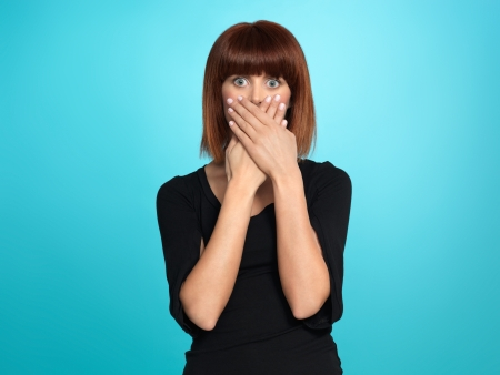 shame: beautiful, young woman, with a surprised face expression, covering her mouth, on blue background