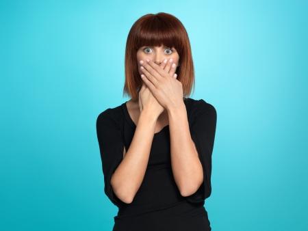 avergonzado: mujer hermosa, joven, con una expresión de la cara de sorpresa, tapándose la boca, sobre fondo azul