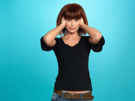 beautiful, young woman covering her ears with her hands, on blue background photo