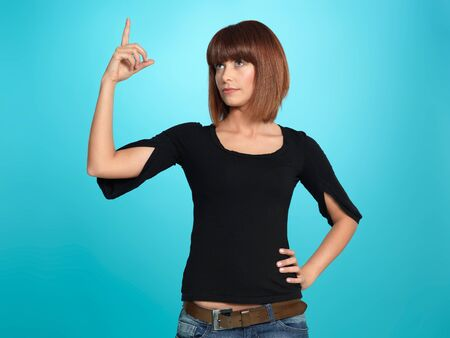 beautiful, young woman having an idea, pointing up, on blue background Stock Photo - 13239386