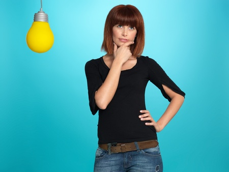 beautiful, young woman thinking of an idea, with a big, yellow lightbulb, on blue background Stock Photo - 13239933