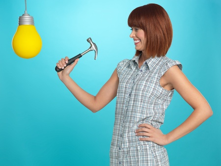 beautiful, young woman smiling, smashing a lightbulb with a hammer, on blue background photo