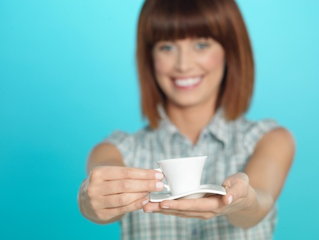 beautiful young woman, holding a small espresso coffee, smiling, on blue background Stock Photo - 13239549