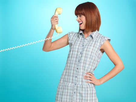 beautiful young woman, having a surprised face expression while talking on the telephone, on blue background photo