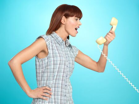 beautiful young woman, screaming on the telephone, on blue background