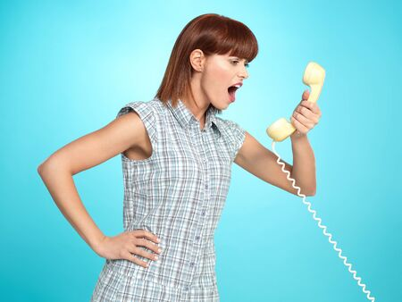 beautiful young woman, screaming on the telephone, on blue background photo