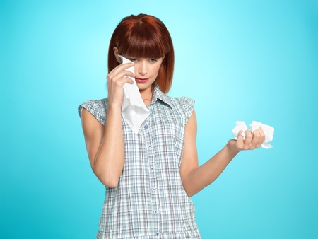 beautiful young woman, crying, wiping her tears with napkins, on blue background photo
