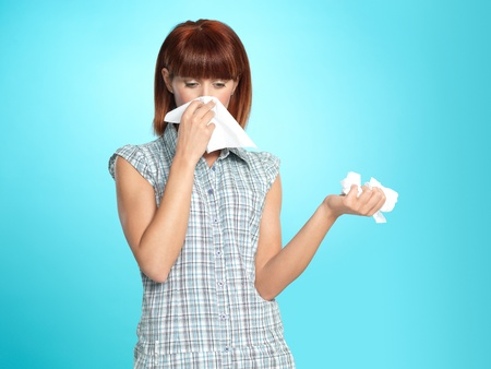 beautiful young woman, crying, blowing her nose, on blue background Stok Fotoğraf