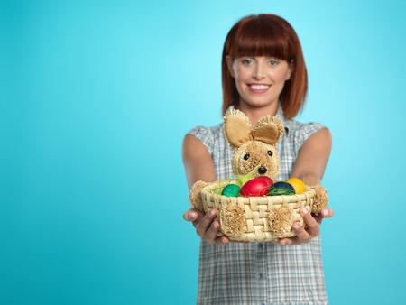 generosity: joven y bella mujer, sosteniendo una canasta con huevos de Pascua, sonriente, sobre fondo azul