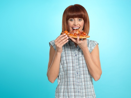 beautiful young woman, eating a slice of pizza, smiling, on blue background Stock Photo - 13239979