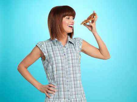 beautiful young woman, eating a slice of pizza, smiling, on blue background Stock Photo - 13240303