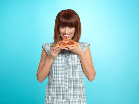 beautiful young woman, eating a slice of pizza, smiling, on blue background Stock Photo - 13239952