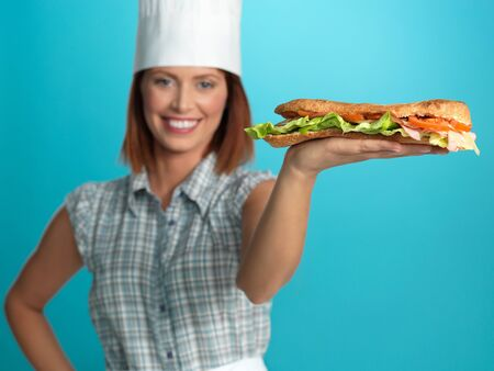 portrait of beautiful young woman chef, holding a big sandwich on one of her hands, on blue background photo