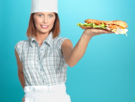portrait of beautiful young woman chef, holding a big sandwich in one of her hands, on blue background photo