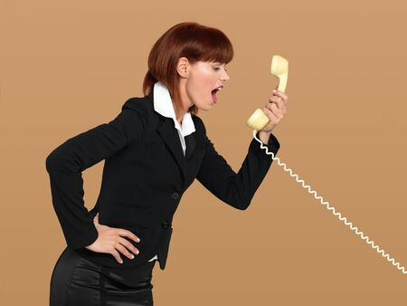 portrait of a stressed, young businesswoman, screaming to the telephone, on beige background photo