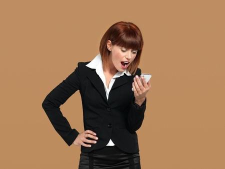 portrait of a stressed, young businesswoman, screaming to her mobile phone, on beige background photo
