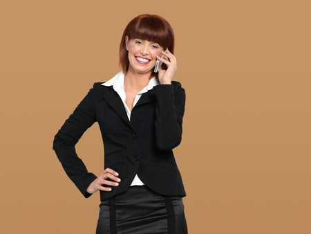 portrait of a happy, young businesswoman, talking to her mobile phone, on beige background photo
