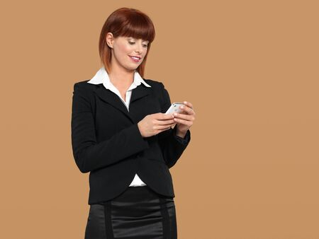 portrait of a happy, young businesswoman, texting on her mobile phone, on beige background Stock Photo - 13239392