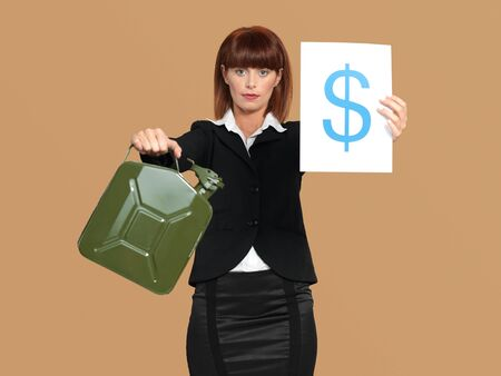 portrait of a young businesswoman, holding a gas canister and a dollar sign in her hands, on beige background photo