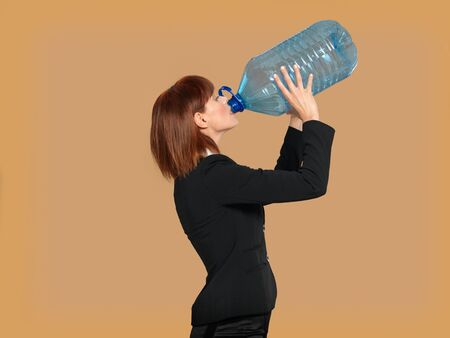 portrait of a young businesswoman, drinking water from a big bottle, on beige background photo