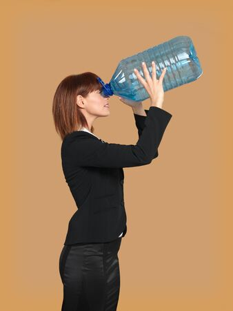 portrait of a young businesswoman, looking through a big, empty water bottle, on beige background photo
