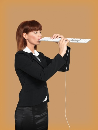 conputer: funny portrait of a young businesswoman, playing and singing on a computer keyboard, on beige background Stock Photo