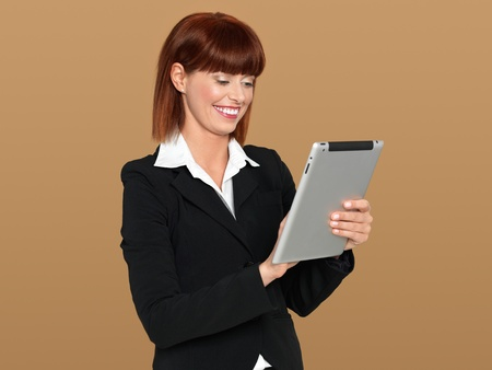 portrait of a beautiful, young businesswoman, working on an electronic computer pad, smiling, on beige background photo